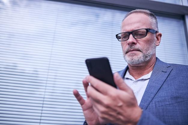 거리에서 현대적인 스마트폰을 사용하는 잘생긴 남자