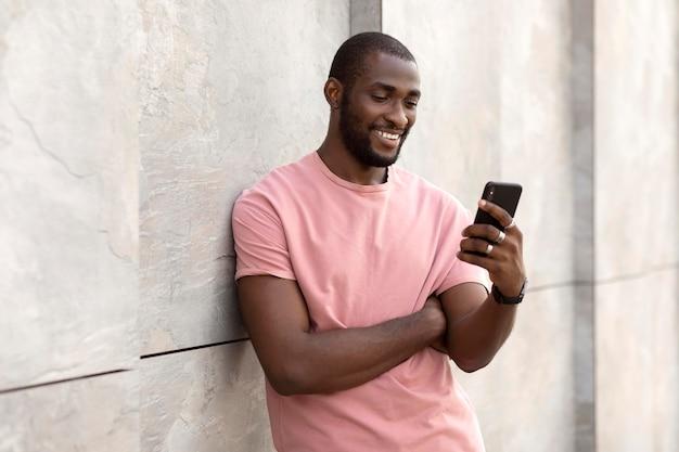 야외에서 현대 스마트폰을 사용하는 잘생긴 남자