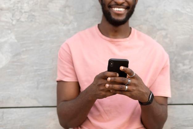 Красивый мужчина с помощью современного смартфона на открытом воздухе