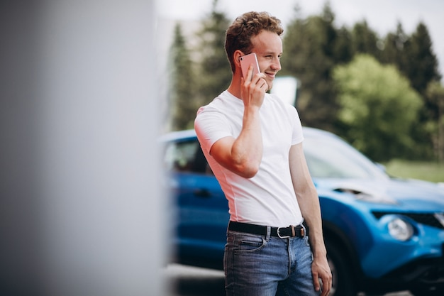 Handsome man using phone by the car