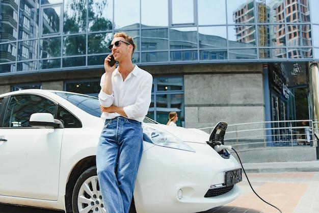 Красивый мужчина с помощью телефона во время зарядки автомобиля