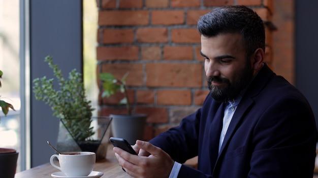 Красивый мужчина с помощью смартфона, пить кофе в кафе