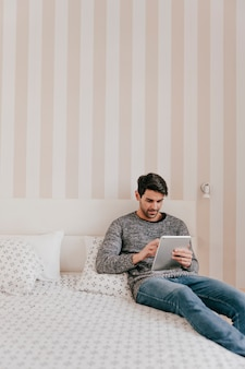Handsome man using tablet in bedroom