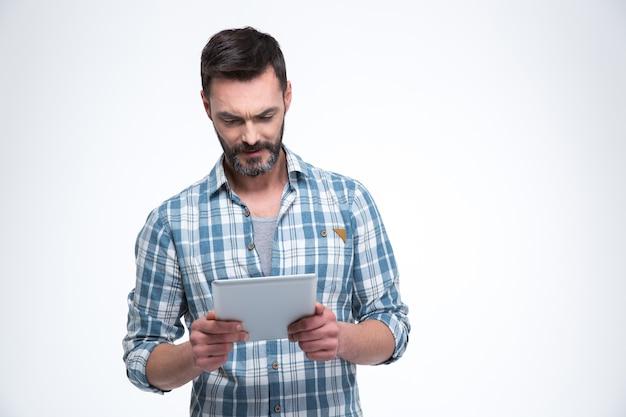 白い壁に分離されたタブレットコンピューターを使用してハンサムな男