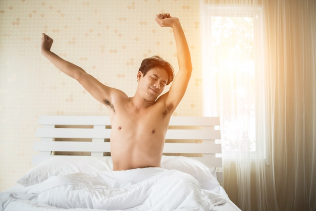 Handsome man wake up and raising hand on the ben in the morning