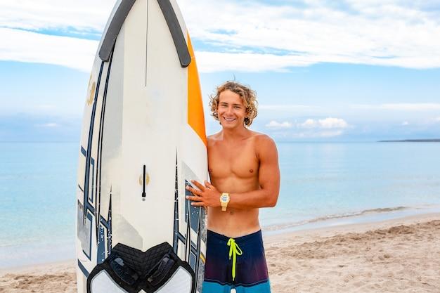 Красивый мужчина гуляет с белой пустой доской для серфинга, ожидая волны, чтобы заняться серфингом на берегу моря