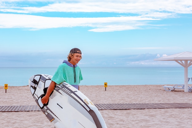 Handsome man walk with white blank surfing board wait for wave to surf spot at sea ocean shore. view from side. concept of sport, fitness, freedom, happiness, new modern life, hipster.