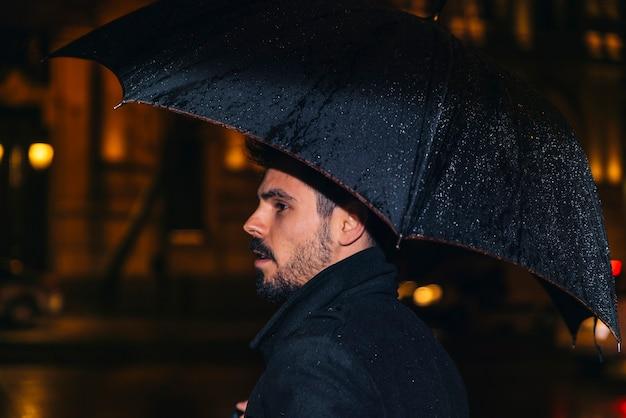 雨の中で夜にマドリードを歩いているハンサムな男。