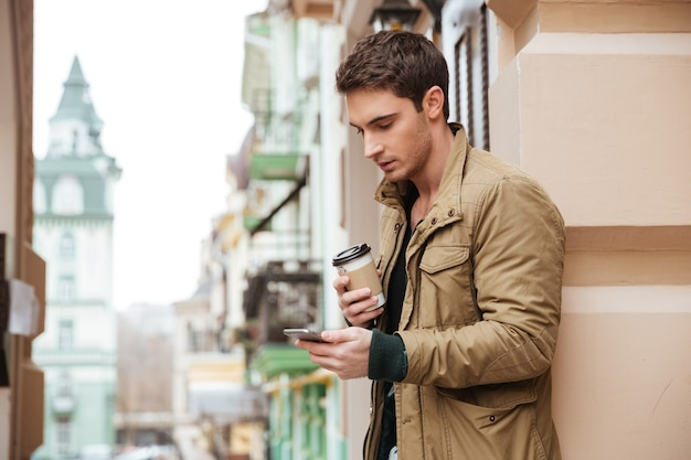 Handsome man walking on street and chatting by his phone outdoors while drinking coffee. look at phone.