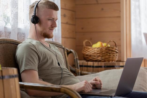 居間でラップトップを使用してオンラインで映画を見ているハンサムな男