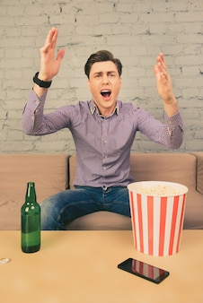 Handsome man watching football with beer and popcorn and screaming