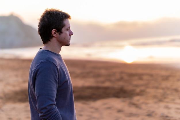 スペインの春のビーチで夕日を見ているハンサムな男。聖週間の休日の概念