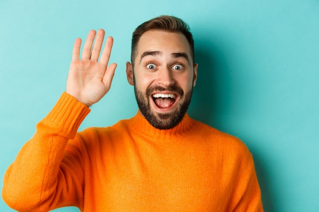 Handsome man waving hand to say hello, giving high five, standing over light blue background.