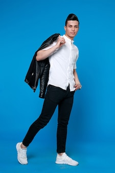 Handsome man wear black leather jacket. full length photo of a young casual man standing with his jacket on his shoulder and his hand in his pocket while looking into the camera. on blue background