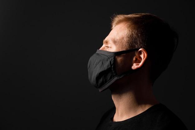잘 생긴 남자는 회색 배경에 코로나 바이러스에 검은 의료 마스크를 착용