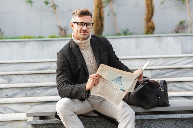 Красивый мужчина в пальто сидит на открытом воздухе и читает газету