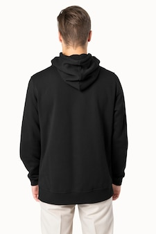Красивый мужчина в черной толстовке с капюшоном для зимней моды, вид сзади