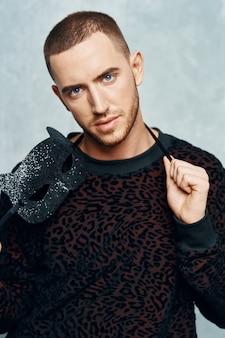 Красивый мужчина в черном свитере, мода, уверенность, позирует на светлом фоне