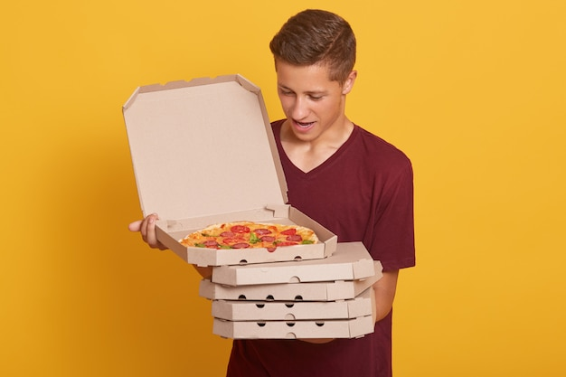 Handsome man wearing burgundy casual t shirt, holding stack of pizza boxes in hands