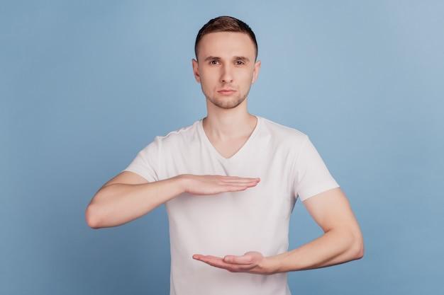 Красивый мужчина в повседневной одежде, жестикулирующий руками, показывающими символ меры знака большого и большого размера, изолированный на синем фоне