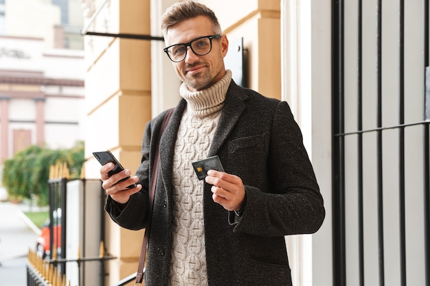 Handsome man wearing a coat walking outdoors, shopping online with mobile phone and credit card