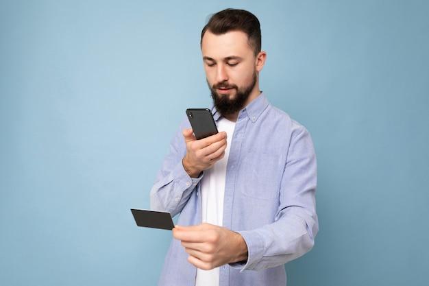 잘 생긴 남자는 배경 벽에 고립 된 일상적인 옷을 입고 스마트 폰 화면을보고 전화 및 신용 카드 결제를 사용하여,