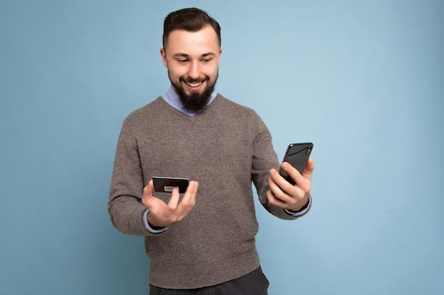 배경 벽에 격리된 일상적인 옷을 입은 잘생긴 남자는 스마트폰 화면을 보고 결제하는 전화와 신용 카드를 사용합니다.