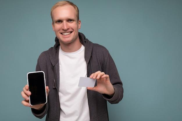 배경 벽 잡고 전화 및 신용 카드 결제를 사용하여 일상적인 옷을 입고 잘 생긴 남자