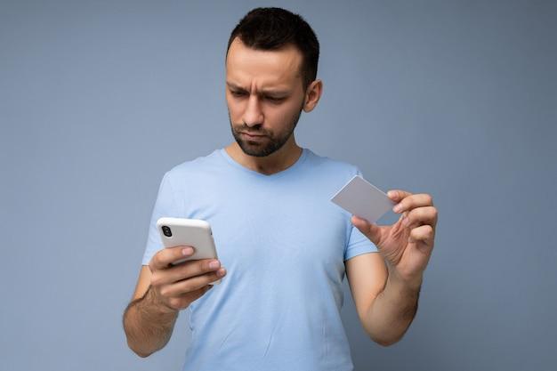 배경 벽에 격리된 일상적인 옷을 입고 전화와 신용을 사용하는 잘생긴 남자