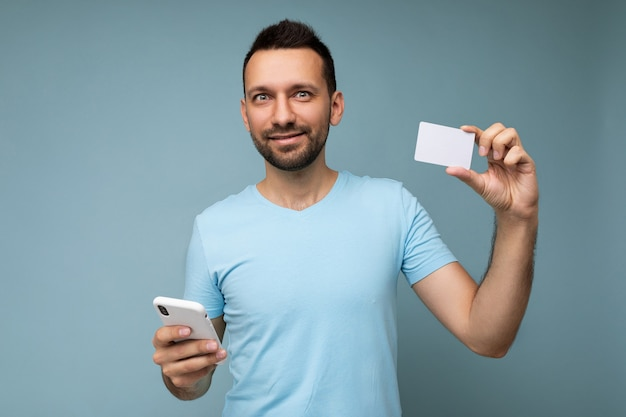 Handsome man wearing everyday clothes isolated on wall holding and using phone and credit card making payment looking at camera.