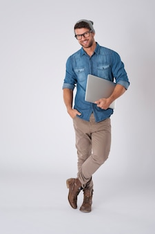 Handsome man wearing fashion glasses and wool hat with laptop