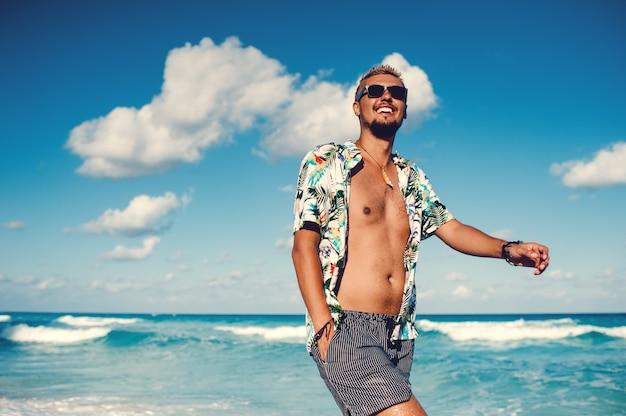 Красивый мужчина в гавайской рубашке на фоне моря или океана