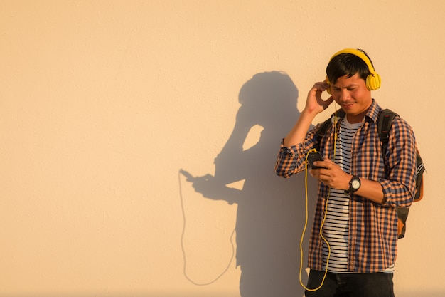 A handsome man wearing headphones and holding a cell phone while standing with an orange w