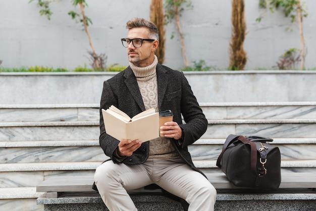Красивый мужчина в куртке, читая книгу, сидя на открытом воздухе