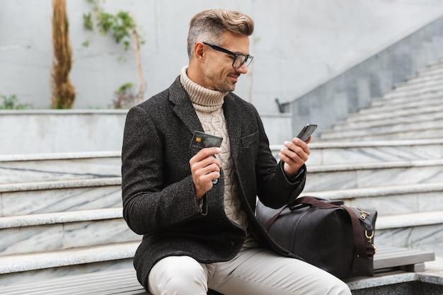 屋外に座っている間携帯電話とクレジットカードでオンラインショッピングのジャケットを着ているハンサムな男