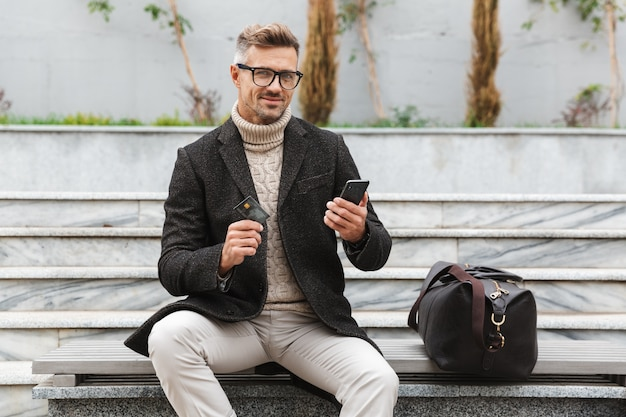 Handsome man wearing jacket shopping online with mobile phone and credit card while sitting outdoors