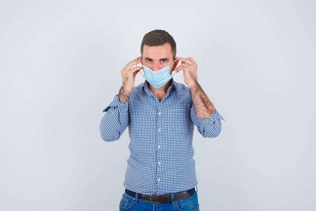 Uomo bello che indossa la maschera in camicia, jeans e che sembra serio, vista frontale.