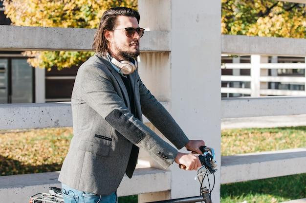 Красивый мужчина в темных очках езда на велосипеде