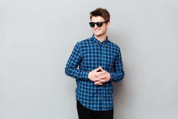 Handsome man wearing sunglasses standing over grey wall