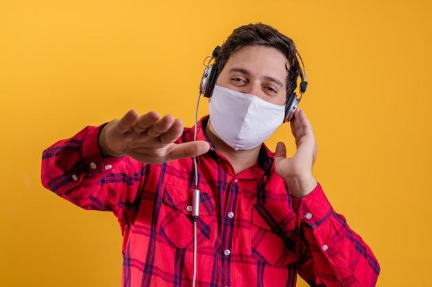 Covidとヘッドフォンから保護するためにサージカルマスクを身に着けているハンサムな男