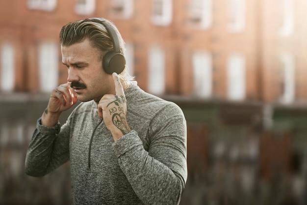 街のリミックスメディアでワイヤレスヘッドフォンを身に着けているハンサムな男