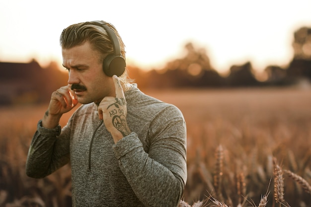 Красивый мужчина в беспроводных наушниках с видом на природу, ремикс медиа