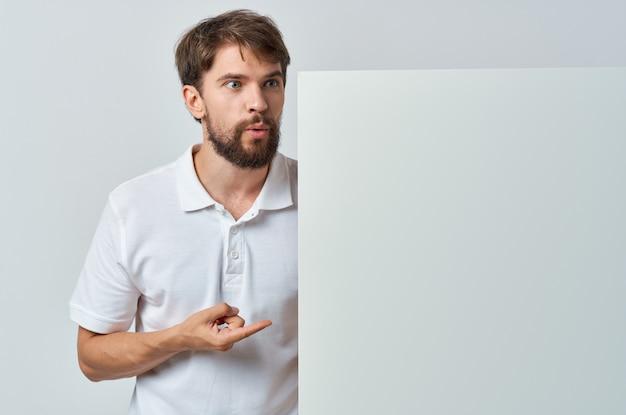 手空白シートプレゼンテーションコピースペーススタジオでハンサムな男の白いバナー。高品質の写真