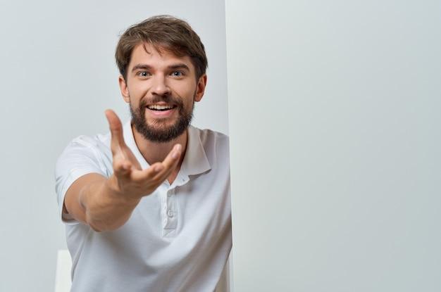 ハンサムな男の白いバナーを手に空白のシートプレゼンテーションコピースペーススタジオ Premium写真