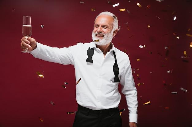 Un bell'uomo in camicia bianca tiene in mano un bicchiere di champagne e posa sul muro bordeaux
