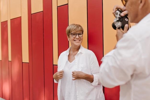 Uomo bello in camicia bianca che fotografa donna positiva con capelli corti biondi in abiti leggeri su arancione e rosso.