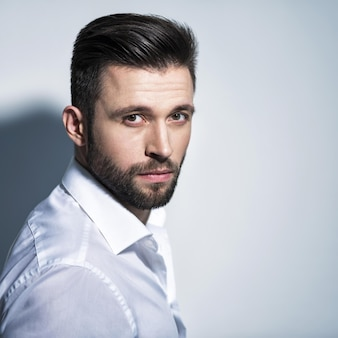 Handsome man in white shirt, posing   attractive guy with fashion hairstyle.  confident man with short beard. adult boy with brown hair. closeup portrait.
