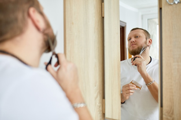 Handsome man in white t-shirt cutting beard himself with scissors at home