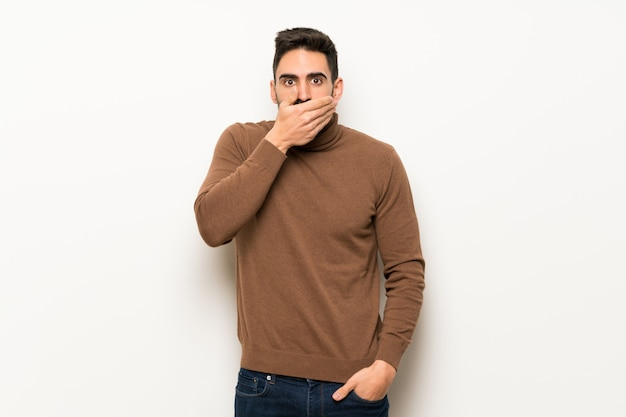 Handsome man over white wall covering mouth with hands for saying something inappropriate