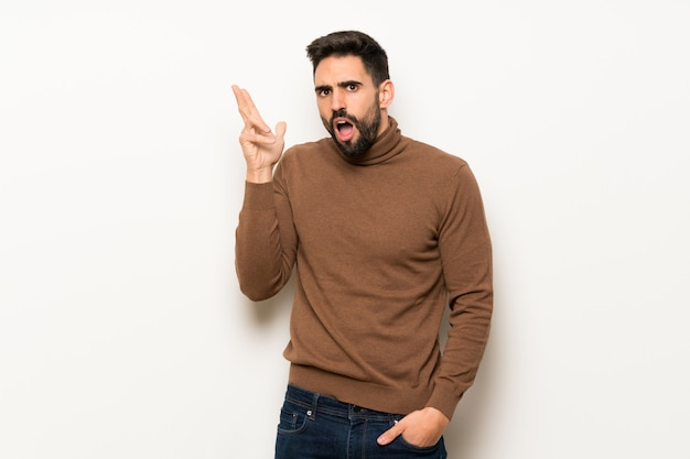 Handsome man over white wall surprised and shocked while looking right